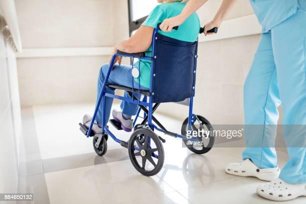 Faible section d'infirmier/infirmière en poussant le patient sur le fauteuil roulant