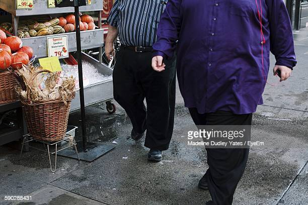 Low Section Of Overweight Men Walking By Market Stall