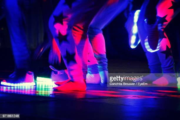 low section of people dancing on illuminated stage - dance floor stock pictures, royalty-free photos & images