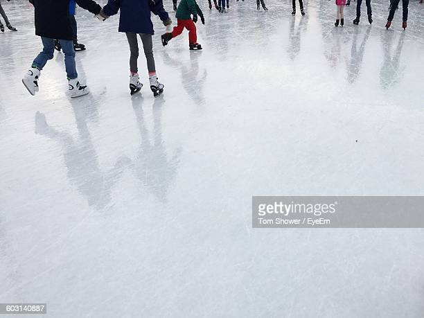 Low Section Of People Ice Skating At Park