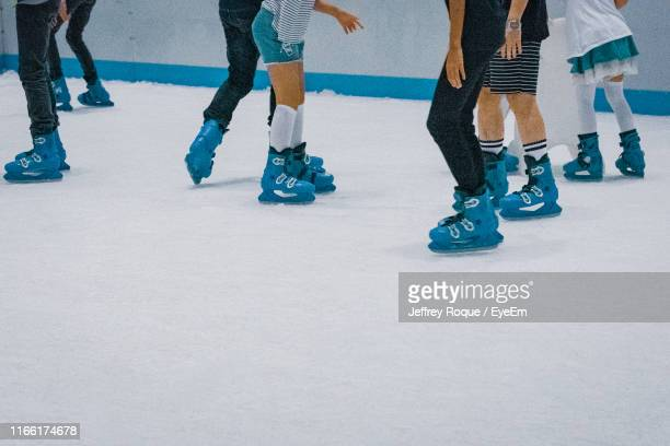 low section of people ice skating - jeffrey roque stock photos and pictures