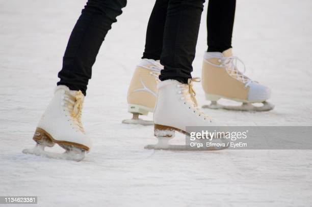 low section of people ice-skating on rink - ice rink stock pictures, royalty-free photos & images
