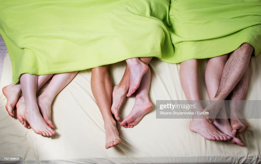 Low Section Of People In Bed : Stock Photo