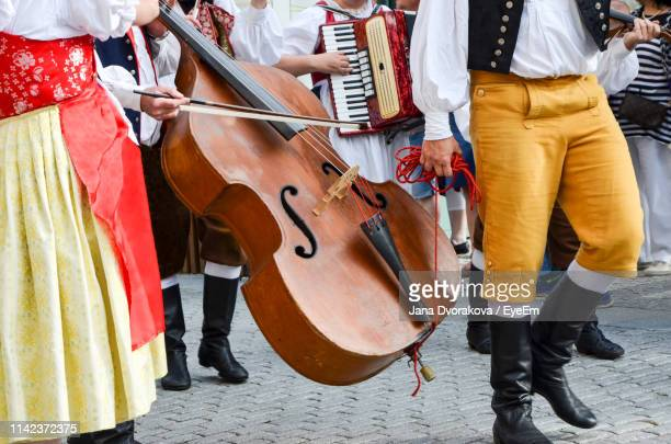 low section of people in traditional clothes on street at city - accordion instrument stock pictures, royalty-free photos & images