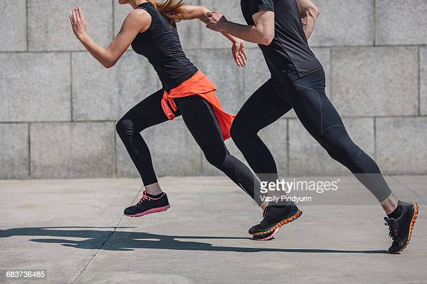 low section of people jogging on sidewalk by wall - jogging stock photos and pictures