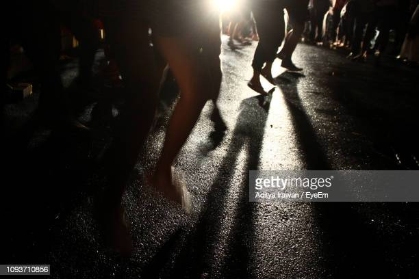 low section of people jumping on road during protest on street at night - protestor stock pictures, royalty-free photos & images