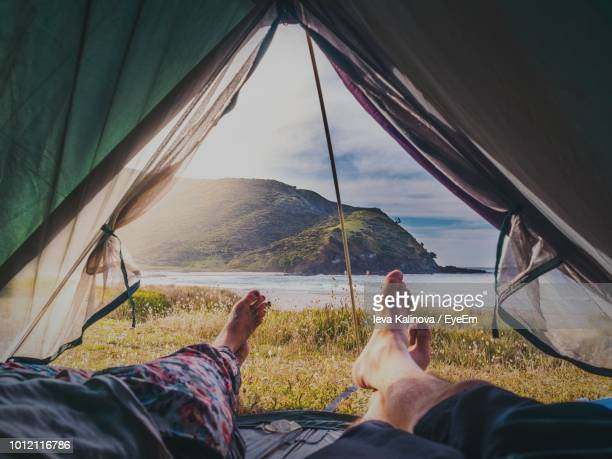 low section of people lying in tent against mountain and sea - camping stock-fotos und bilder