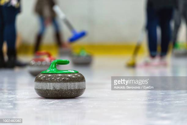 low section of people playing curling on ice rink - curling sport stock pictures, royalty-free photos & images
