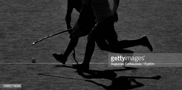 low section of people playing hockey on field - field hockey stock pictures, royalty-free photos & images