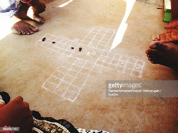 Low Section Of People Playing Old-Fashioned Ludo On Floor