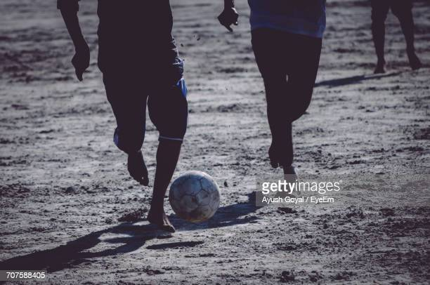 Low Section Of People Playing Soccer On Beach