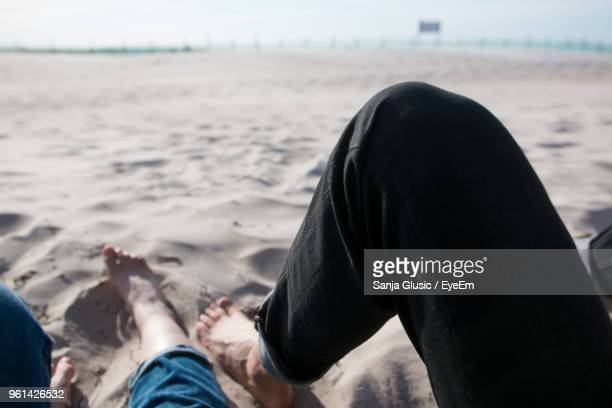 Low Section Of People Relaxing At Beach