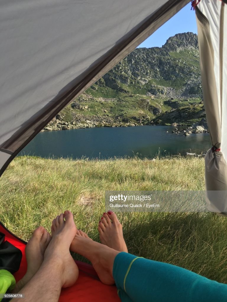 Low Section Of People Relaxing In Tent : Stock Photo