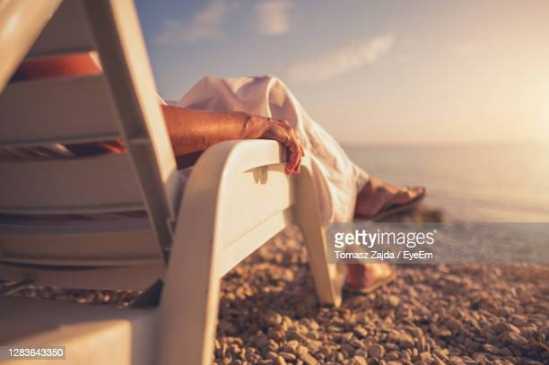 low section of people relaxing on beach - human leg stock pictures, royalty-free photos & images