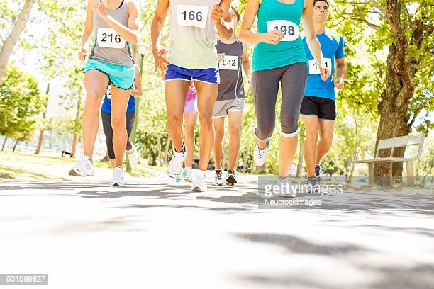 low section of people running marathon at park - 10000 meter stock pictures, royalty-free photos & images