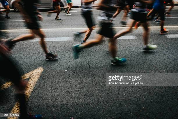 low section of people running on road in city - maratona foto e immagini stock