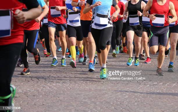 low section of people running on road - marathon stock pictures, royalty-free photos & images
