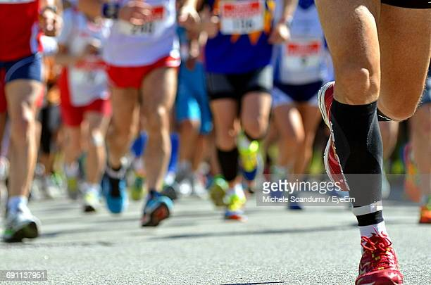 low section of people running on street in marathon - maratona foto e immagini stock