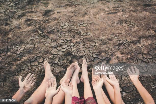 low section of people sitting on arid field - extremlandschaft stock-fotos und bilder