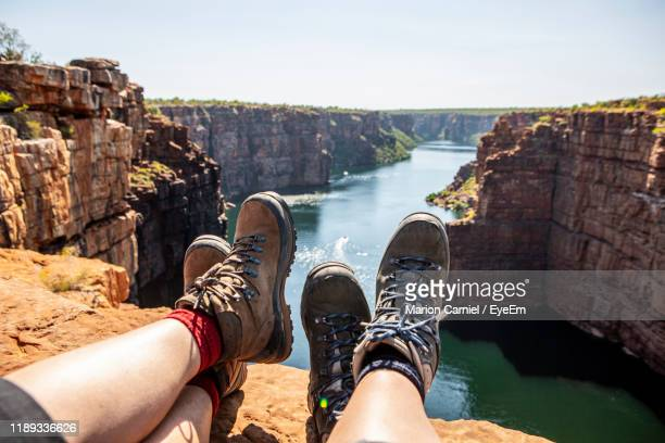 low section of people sitting on rock by river against sky - western australia stock-fotos und bilder