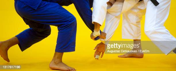 low section of people standing against yellow wall - judo stock pictures, royalty-free photos & images