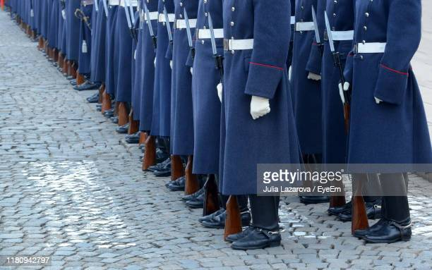 low section of people standing on footpath in city - military uniform stock pictures, royalty-free photos & images