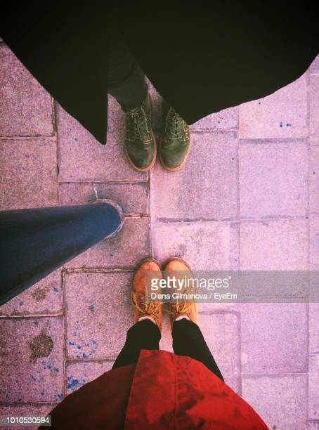 low section of people standing on footpath - sezione inferiore foto e immagini stock
