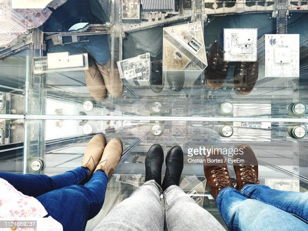 low section of people standing on glass over cityscape - cook county illinois stock photos and pictures