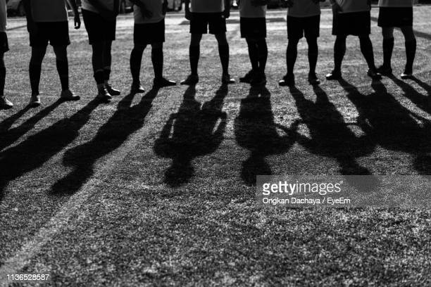 low section of people standing on soccer field - team sport stock pictures, royalty-free photos & images