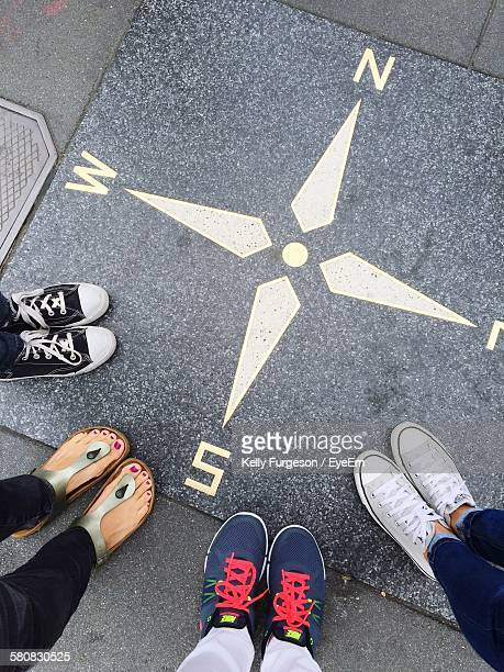 low section of people standing on street by navigational compass - unterer teil stock-fotos und bilder