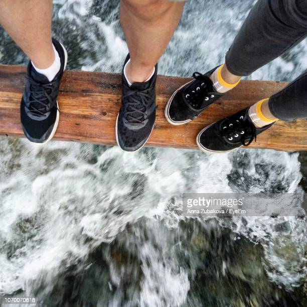 Low Section Of People Standing On Wooden Plank Over Flowing River