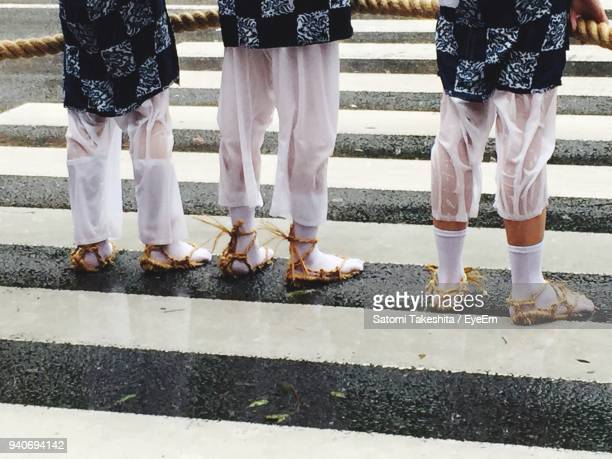 Low Section Of People Standing On Zebra Crossing During Rainy Season