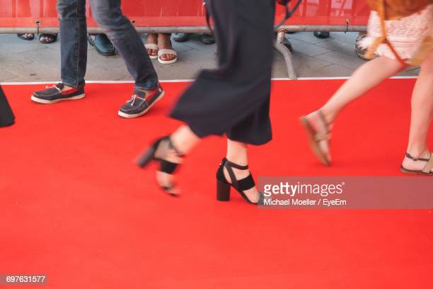low section of people walking at red carpet event - red carpet event photos et images de collection