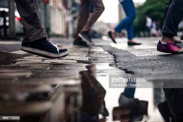 Low Section Of People Walking By Puddle