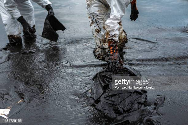 low section of people walking in water - oil spill stock pictures, royalty-free photos & images
