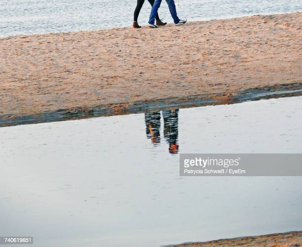 Low Section Of People Walking On Beach