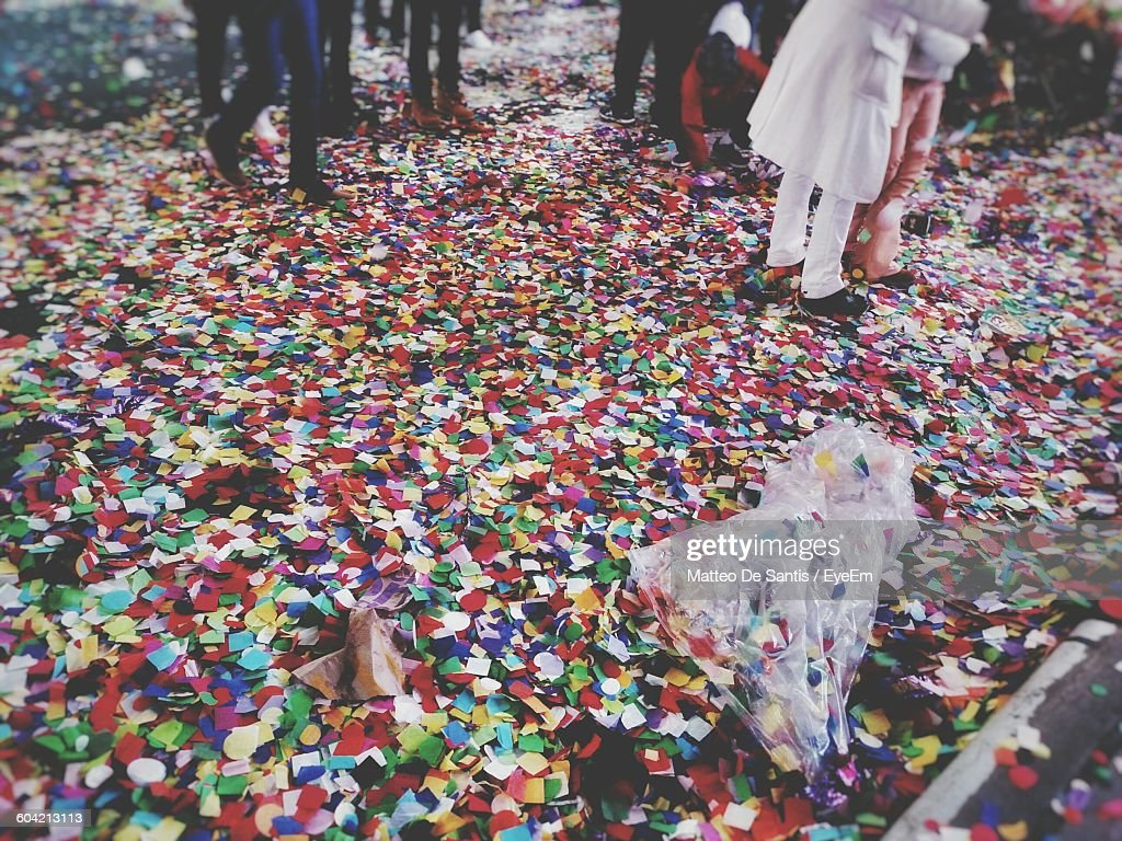 Low Section Of People Walking On Confetti Covered Street : Stock Photo