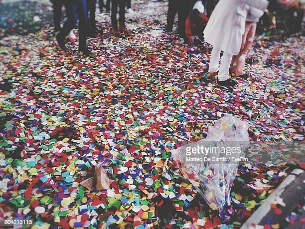 Low Section Of People Walking On Confetti Covered Street