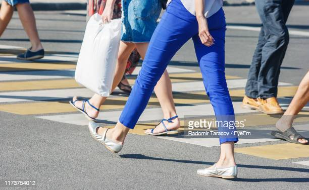 low section of people walking on crosswalk - low section stock pictures, royalty-free photos & images