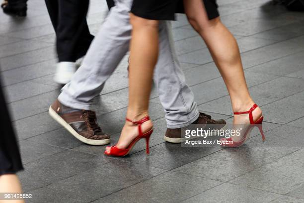 low section of people walking on footpath in city - human leg stock photos and pictures
