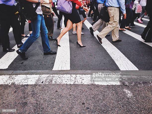 Low Section Of People Walking On Pedestrian Crossing On Street In City