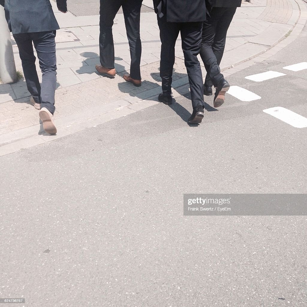 Low Section Of People Walking On Road During Sunny Day : Stock-Foto