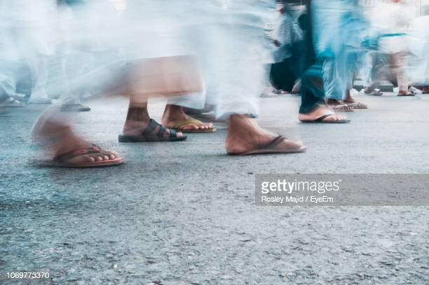 low section of people walking on road - arab feet photos et images de collection