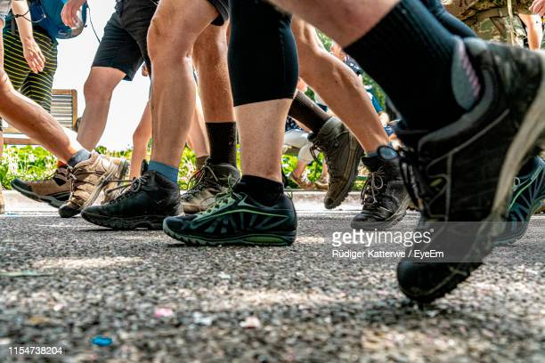 low section of people walking on road - nijmegen stock pictures, royalty-free photos & images