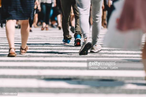 low section of people walking on road - 人の足 ストックフォトと画像