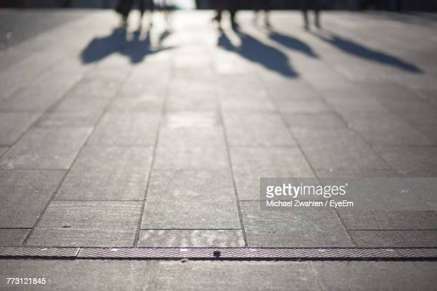 low section of people walking on sidewalk - michael stock photos and pictures
