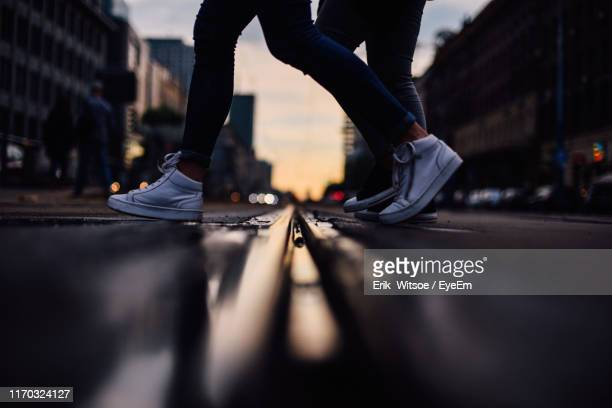 low section of people walking on street city - low section stock pictures, royalty-free photos & images