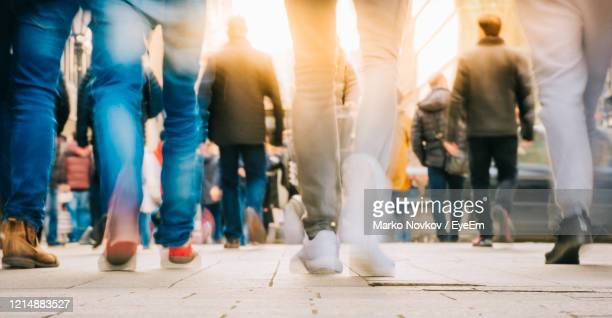 low section of people walking on street in city - grande gruppo di persone foto e immagini stock