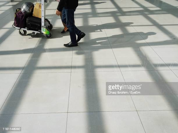 Low Section Of People Walking On Tiled Floor