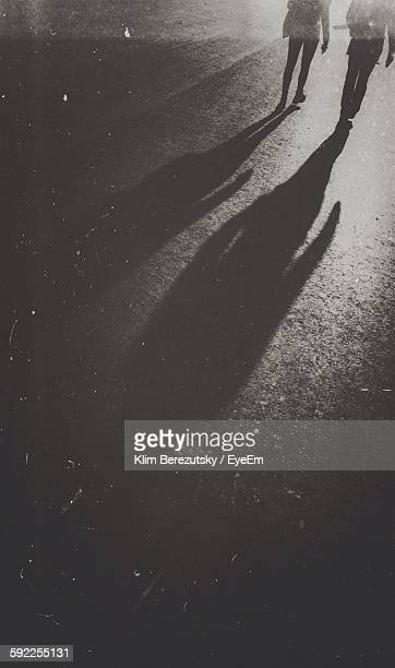 low section of people walking with shadow on footpath in city - sombra em primeiro plano imagens e fotografias de stock